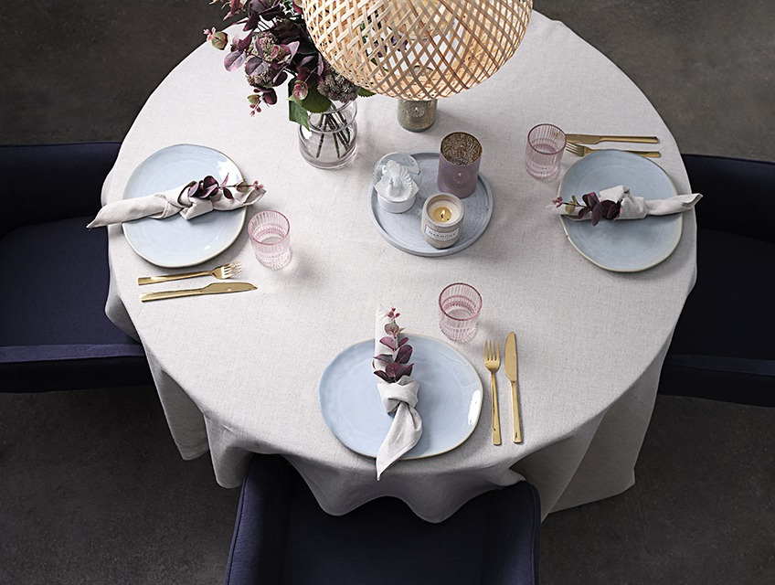 Table set with table cloth, cloth napkins, plates, glasses, vase and candles